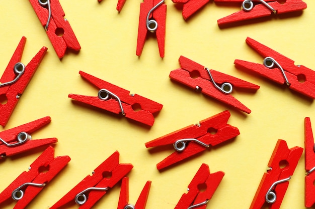Composition of red clothespins on a yellow background.