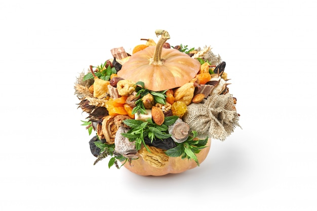 Composition of ripe orange pumpkin filled with sweets and dried fruits on white