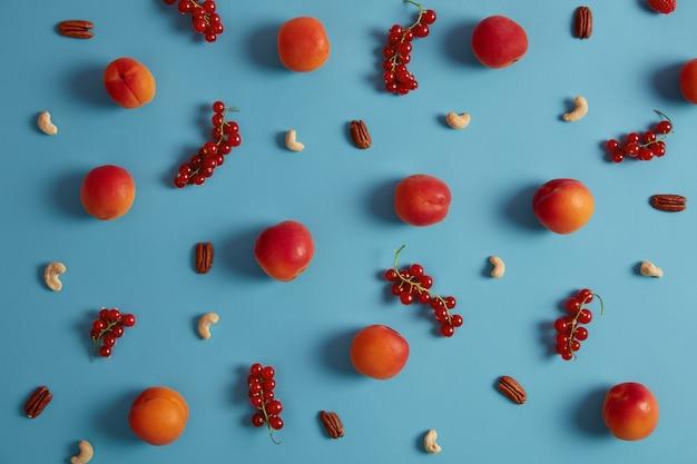 Composizione di ribes rosso maturo, pesche, anacardi e noci. cibo sano e spuntino. ingredienti per preparare un pasto biologico. mangiare pulito. dieta equilibrata. ricco di fibre fonti di prodotti vegani