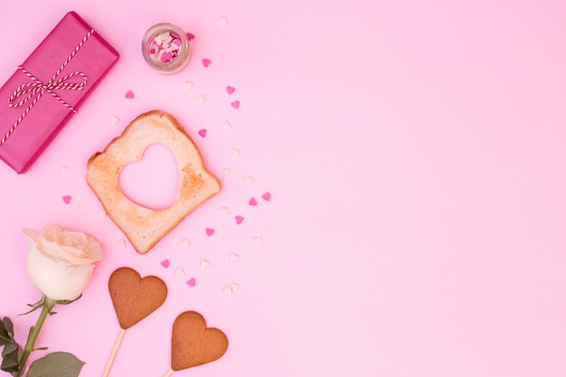 Composition of rose with heart-shaped cookies