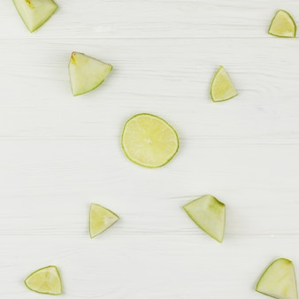 Composition of sliced apples and lime on white background