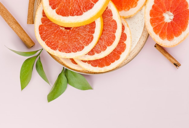 Composition of slices of grapefruit on dish and green leaves near cinnamon
