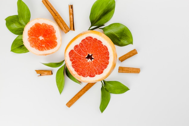 Composition of slices of grapefruit and green leaves near cinnamon