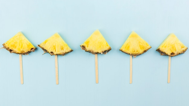 Composition of slices of pineapple on wands