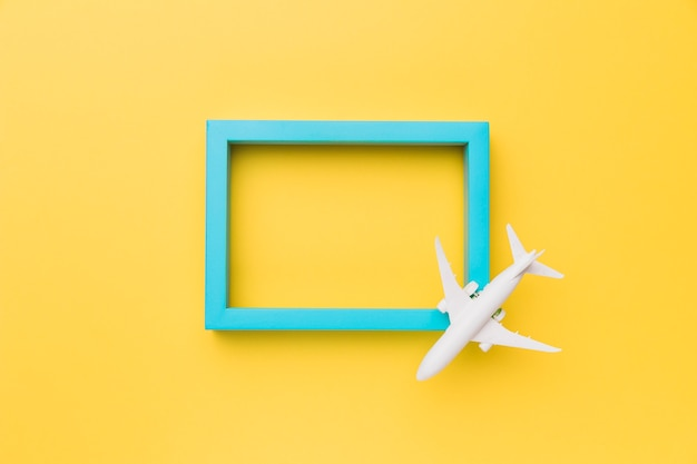 Composition of small airplane on blue frame