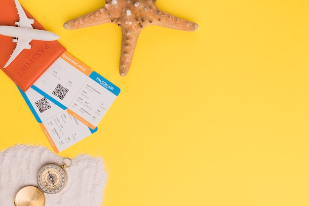 Composition of small plane passport tickets starfish and compass on towel