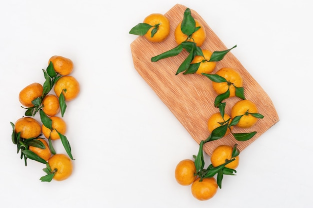 Composition of small tangerines with green leaves on white
