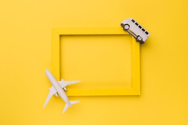 Composition of small white plane and bus on yellow frame