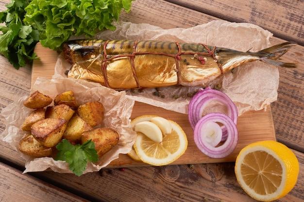 Композиция из копченой скумбрии с гарниром из картофеля, лимона, зелени, лука, подается на деревянной доске, вид сверху