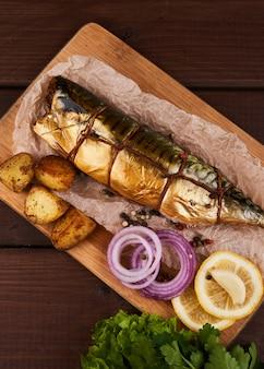 Композиция копченая скумбрия с гарниром из картофеля, лимона, зелени, лука, подается на деревянной доске, вид сверху