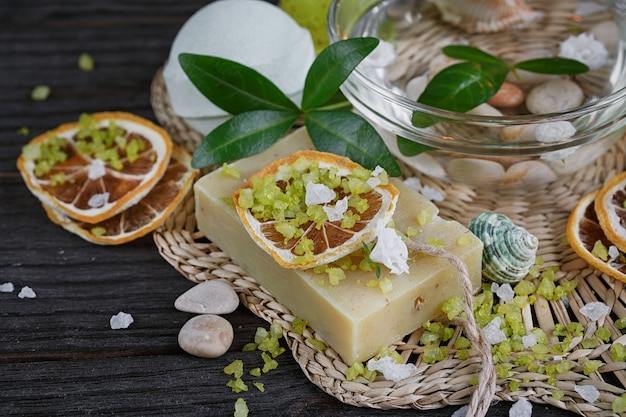 Composition of spa treatment with green salt and soap on wooden surface