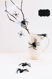 Composition of spiders and jug with branch