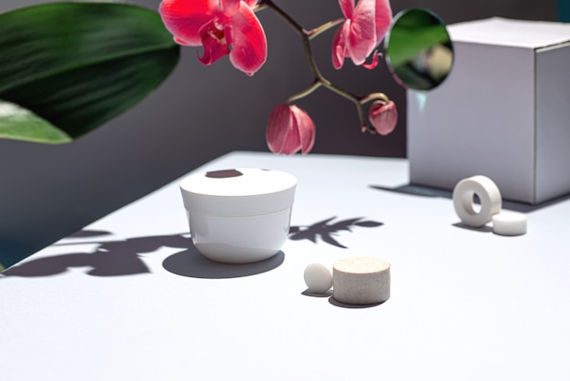 Composition on the table with cream and orchid flower.