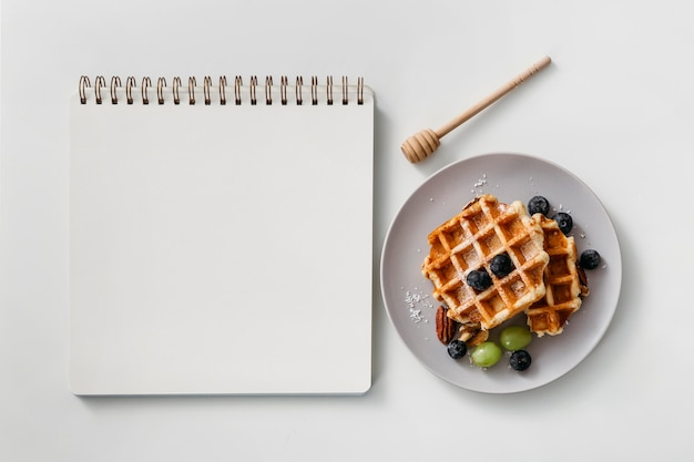 Composition of tasty breakfast waffles with empty notebook