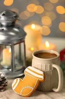 Composition of tasty gingerbread cookie, mug and christmas decor
