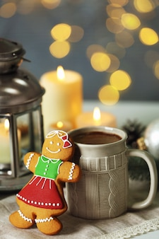 Composition of tasty gingerbread cookie and mug with cocoa