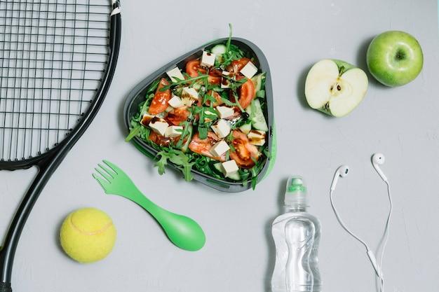 Composizione di attrezzatura da tennis e cibo utile