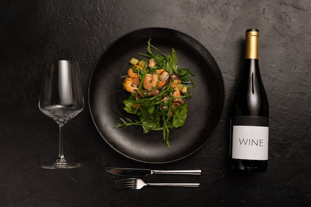 Composition on the theme of decorating a restaurant menu with appetizers from a salad, a bottle of wine, a glass and cutlery on a black stone table.