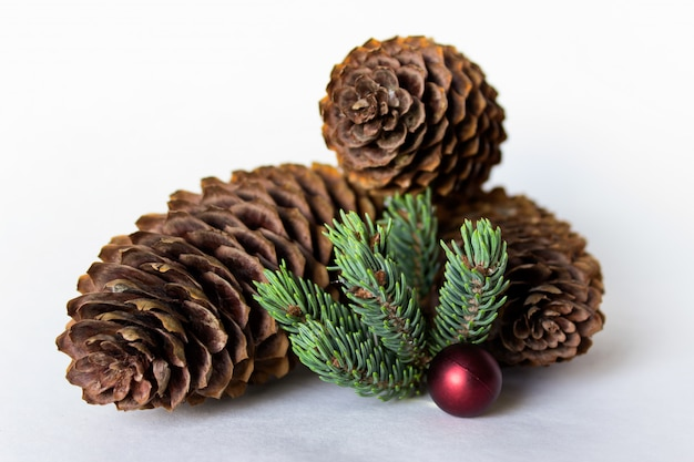 Composition of three pine cones with red ball decoration and pine twig isolated on white background.