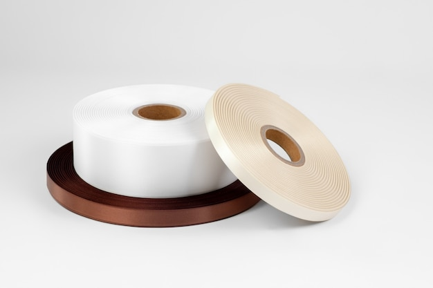 Composition of three reels of satin ribbons for labels or sewing in white dark brown and beige isolated