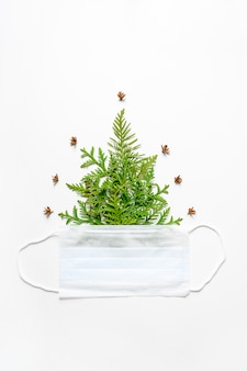 Composition of thuja twigs in the form of a christmas tree, and a medical mask isolated on a white background. concept of the new year during the corona virus covid-19.