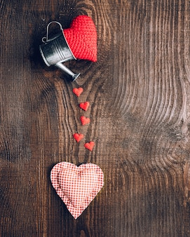 Composition of tissue hearts and decorative buckets on a dark wooden background