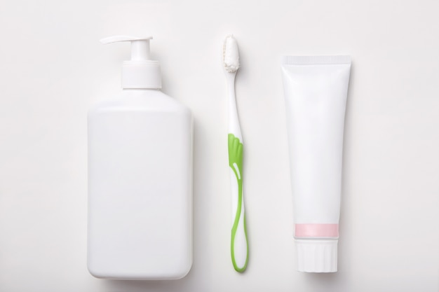 Composition of toothbrush, toothpaste and bottle of soap or gel isolated on white. cosmetic products. flat lay
