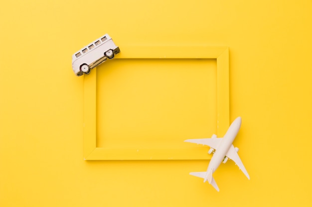 Composition of toy airplane and bus on yellow frame