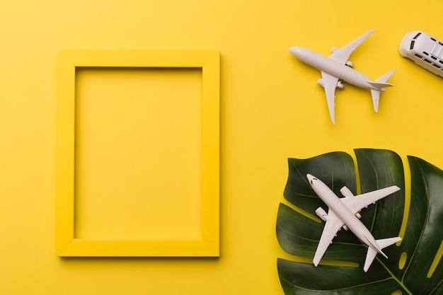 Composition of toy jets bus yellow frame and plant leaf