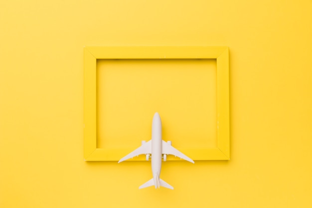 Composition of toy plane on yellow frame