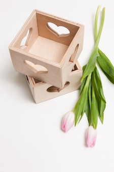 Composition of tulips and decorative wooden boxes with heart shaped hole on white table, top view, free space. floristics workshop, flower arrangement, presents and holiday gift concept