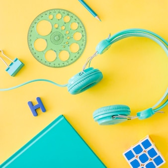 Composition of turquoise accessories on yellow background