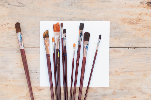 Composition of used paintbrushes on white paper