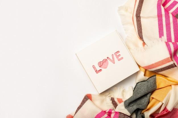 作曲バレンタインデー。白い背景の上の贈り物とスカーフ。バナー。フラットレイ、上面図。