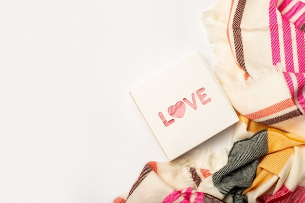 Composition valentine's day. gift and scarf on a white background. banner. flat lay, top view.