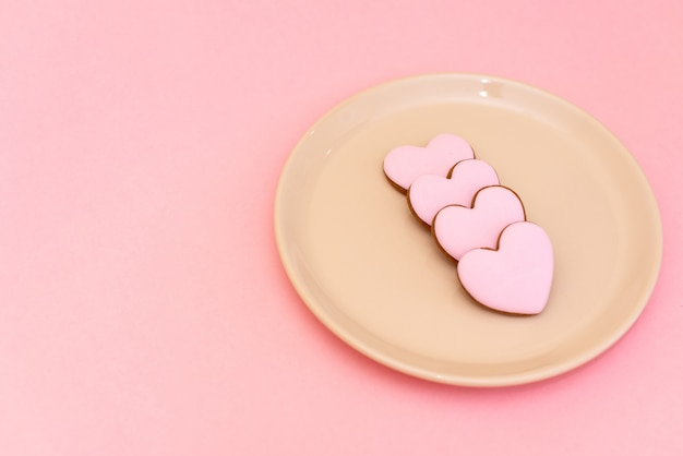 Composition valentine's day. ginger cookie in shape heart on pastel pink.