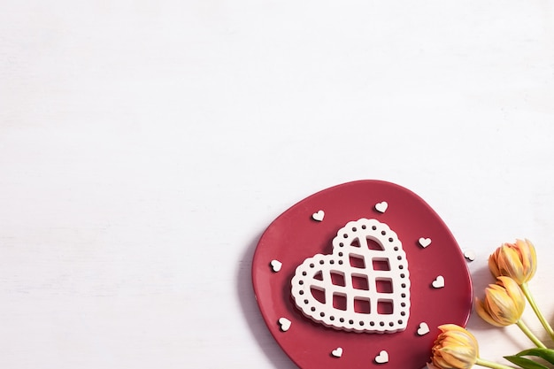 Composition for valentine's day with plate, flowers and decor element top view.
