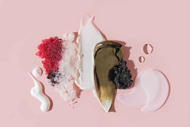 Composition of various cosmetic mask, creams, serum, scrub and lotion smear on a pink background. beauty texture. sample of a cosmetic product.
