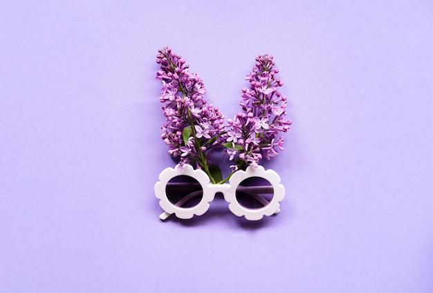 Composition of white modern sunglasses with lilac flowers. summer creative concept. flat lay. top view