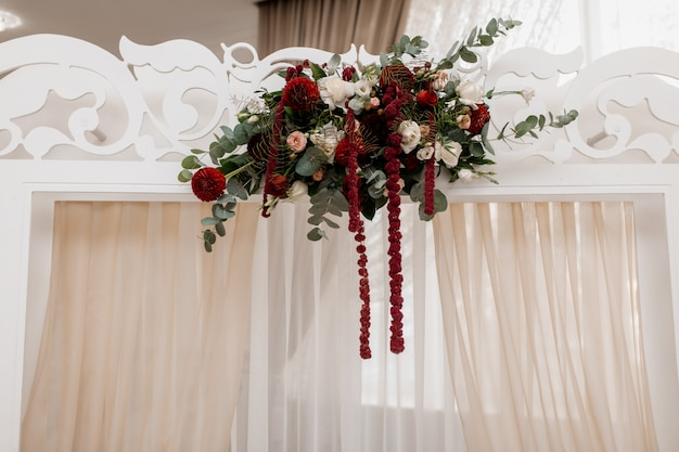 Composition on the white wedding arch made of eucalyptus and bordeaux flowers