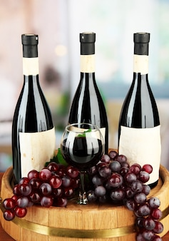 Composition of wine bottles, glass and  grape,on wooden barrel, on bright