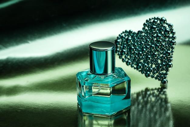 光沢のあるターコイズブルーの背景に香水のボトルを使用した構成