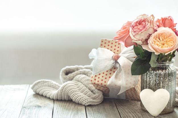Композиция с букетом роз в стеклянной вазе на размытом светлом фоне