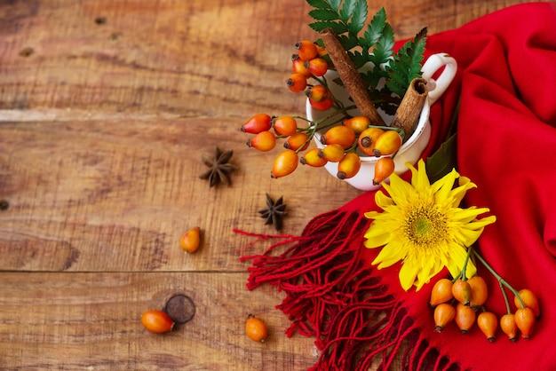 장미 베리, 가문비나무 가지, 해바라기가 나무 배경에 달린 빨간 스카프가 있는 컵으로 구성