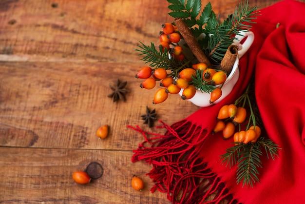 とげのあるベリートウヒの枝と木製の背景に赤いスカーフとカップで構成