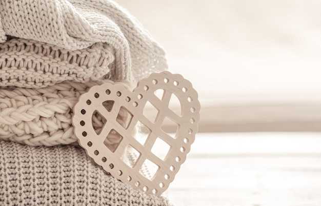 きちんと折りたたまれた暖かい服を背景に装飾的なハートのある構図。バレンタインデーのコンセプト。
