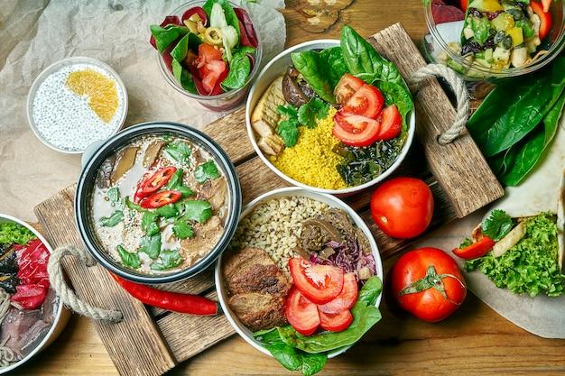 ベジタリアン料理のディナーテーブル付きの構成:ボウル、デザート、灰色の布に味噌汁。健康的でバランスの取れた料理。メニュー写真、上面図