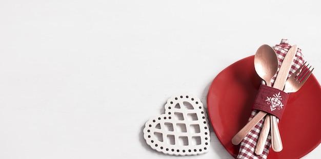 バレンタインデーのロマンチックなディナーのためのプレートとカトラリーで構成。デートのコンセプト。