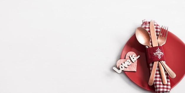 バレンタインデーのトップビューのロマンチックなディナーのためのプレートとカトラリーを備えた構成。デートのコンセプト。