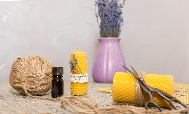 Композиция с аксессуарами для изготовления восковых свечей своими руками: восковая тарелка, ножницы, джут, ароматическое масло, сухоцветы.